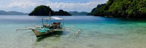 Traditionelles hölzernes philippinisches Boot in einer blauen Lagune Stockfotografie