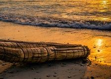 Traditionelles handgemachtes Fischerboot auf Strand bei Sonnenuntergang in Huanchaco, Peru lizenzfreies stockfoto