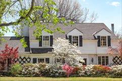 Traditionelles hochwertiges Haus mit Hartriegel Baum- und azeleabüschen - b stockfotos