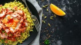Traditionelles Indisch-englisches kedgeree Frühstück: Basmatireis mit Ei Benedict und heißen geräucherten süßen Paprikalachsen stockfotos