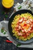 Traditionelles Indisch-englisches kedgeree Frühstück: Basmatireis mit Ei Benedict und heißen geräucherten süßen Paprikalachsen stockfoto