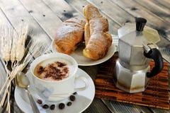 Traditionelles italienisches Frühstück mit Cappuccino und Hörnchen auf einem rustikalen Holztisch stockbild