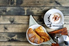 Traditionelles italienisches Frühstück mit Cappuccino und Hörnchen auf einem rustikalen Holztisch stockfoto