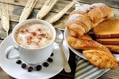 Traditionelles italienisches Frühstück mit Cappuccino und Hörnchen auf einem rustikalen Holztisch lizenzfreie stockfotografie