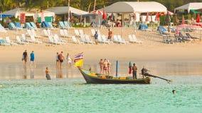 Traditionelles langes hölzernes Motorboot und Touristen gehen auf einen Kamala-Strand auf Ebbezeit mit Strand Stockfotos
