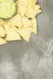 Traditionelles lateinamerikanisches Soßenguacamole in einer Schüssel und in den Nachos Stockfotos