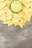 Traditionelles lateinamerikanisches Soßenguacamole in einer Schüssel und in den Nachos Stockbilder