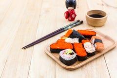 Traditionelles Lebensmittel der japanischen Sushi auf hölzerner Platte mit kokeshi Lizenzfreie Stockfotos
