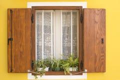 Traditionelles Mittelmeerfenster auf gelber Wand Stockfotografie