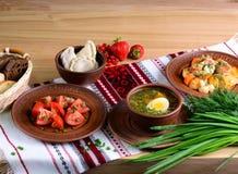 Traditionelles nationales Lebensmittel: Suppe mit Ei, Salat mit Tomaten, vareniki, Gemüseeintopfgericht auf einer Tischdecke mit  Stockfoto
