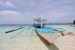 Traditionelles Philippinen-Boot auf dem Seeufer Stockfotos