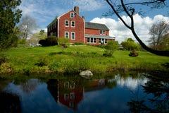 Traditionelles rotes hölzernes Haus auf einem Teich. Lizenzfreies Stockbild