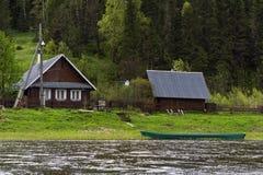 Traditionelles russisches Dorfhaus auf der Flussbank stockbild