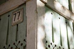 Traditionelles russisches Holzhaus mit Nummernschildnahaufnahme Holz schnitzte Dekorationen auf einem grünen rustikalen Gebäude Lizenzfreies Stockfoto