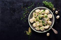 Traditionelles russisches pelmeni, Ravioli, Mehlklöße mit Fleisch auf schwarzem konkretem Hintergrund Petersilie, Wachteleier, Pf stockbilder