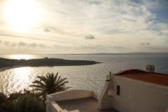 Traditionelles sardinisches Seehaus, das eine atemberaubende Ansicht bei Sonnenuntergang übersieht stockbilder