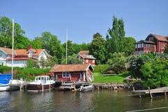 Traditionelles schwedisches Inseldorf und -Segelboote Stockfotos