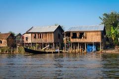 Traditionelles Stelzenhaus und lange Boote im Wasser unter blauem Himmel Stockbild