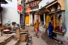 Traditionelles Straßenleben mit Verkäufer, eine betende Frau und Passantleute Lizenzfreie Stockfotos