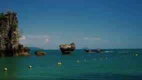 Traditionelles thailändisches Boot des langen Schwanzes, das nahe Felsformationen auf dem Meer überschreitet stock footage