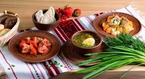 Traditionelles ukrainisches Abendessen: Gemüsesuppe mit gekochtem Ei, Salat mit Tomaten, vareniki, Gemüseeintopfgericht auf Tisch Lizenzfreie Stockbilder