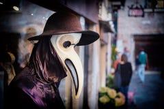 Traditionelles venetianisches Mannequin in Pestdoktorkostüm, Maske und Hut nahe kaufen Fenster in der Straße von Venedig, Italien Stockfotos