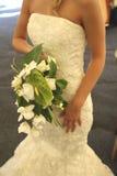Traditionelles weißes Kleid mit einem Blumenstrauß der Blumen Lizenzfreies Stockfoto