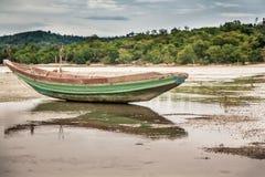 Traditionellt asiatiskt fartyg på stimen under lågvatten på den tropiska stranden i mulen dag royaltyfri foto