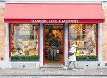 Traditionellt belgiskt handgjort snör åt, och gobelänger shoppar i Brugge arkivbilder