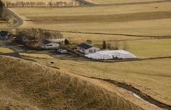Traditionellt bruka i Island Vita runda baler med gräs som ligger nära en lantgård på ett torrt gult gräs i Island arkivfoto