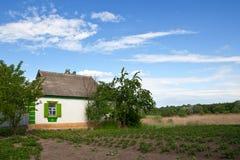 Traditionellt byhus med en trädgård Arkivbild