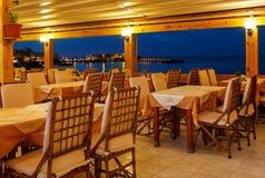Traditionellt europeiskt kafé i natt på ön av den KretaGrekland natten Trästolar med vita borddukar på fjärden arkivfoto
