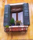 Traditionellt fönster med blommor i den venice gatan, royaltyfri foto