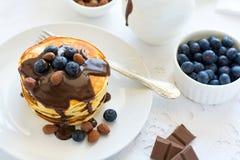 Traditionellt frukostbegrepp Bunt av pannkakor med chokladsås, blåbär och muttrar Royaltyfri Fotografi