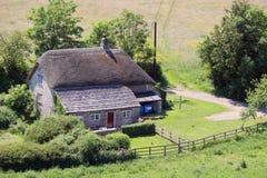 Traditionellt gammalmodigt stenbuijltlantbrukarhem med halmtäckt r arkivfoto