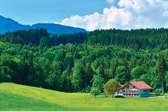 Traditionellt hus för bavarianfamiljlantgård bredvid en skog i den Bayern regionen, Tyskland Royaltyfri Fotografi
