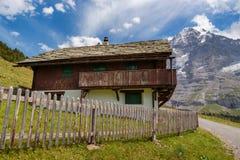 Traditionellt hus i schweiziska fjällängar Arkivbild