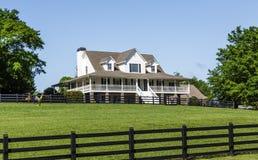 Traditionellt hus utöver grön gräsmatta och det svarta staketet Royaltyfri Fotografi