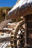 Traditionellt japanskt vatten maler med ett hus för halmtäckt tak i Iyashino-Sato Nenba den traditionella byn som täckas av insnö arkivfoto