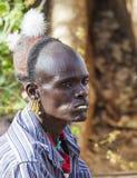 Traditionellt klädd Hamar man med att tugga pinnen i hans mun Arkivbilder
