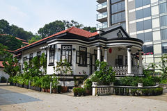 Traditionellt kolonialt hus Singapore bredvid modern highrisebyggnad Royaltyfri Bild