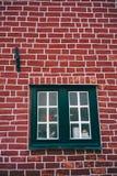 Traditionellt medeltida tyskt tegelstenhus i Luneburg, Tyskland Fragment av fasaden för röd tegelsten med fönsterramar Fotografering för Bildbyråer