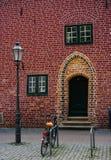 Traditionellt medeltida tyskt tegelstenhus i Luneburg, Tyskland Fragment som klibbar ut ur fasaden Parkerad cykel Arkivfoto