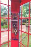 Traditionellt rött gammalt telefonbås för tappning i trädgårds- Thailand royaltyfri bild
