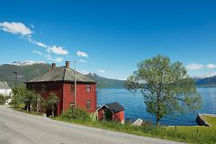 Traditionellt rött målat norskt hus med Sognefjord på bakgrunden i Balestrand, Norge Royaltyfri Bild