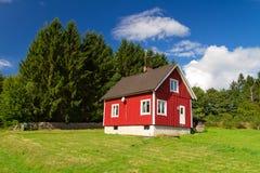 Traditionellt rött svenskt hus på skogen Arkivfoto