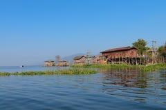 Traditionellt styltahus i vatten under blå himmel arkivbilder
