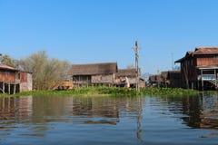 Traditionellt styltahus i vatten under blå himmel Arkivbild