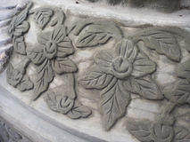 Traditionellt thailändskt snida av blommor på tempelväggen Arkivfoton