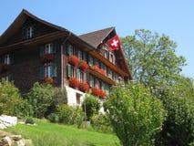 Traditionellt träschweizarehus med flaggan Royaltyfri Bild